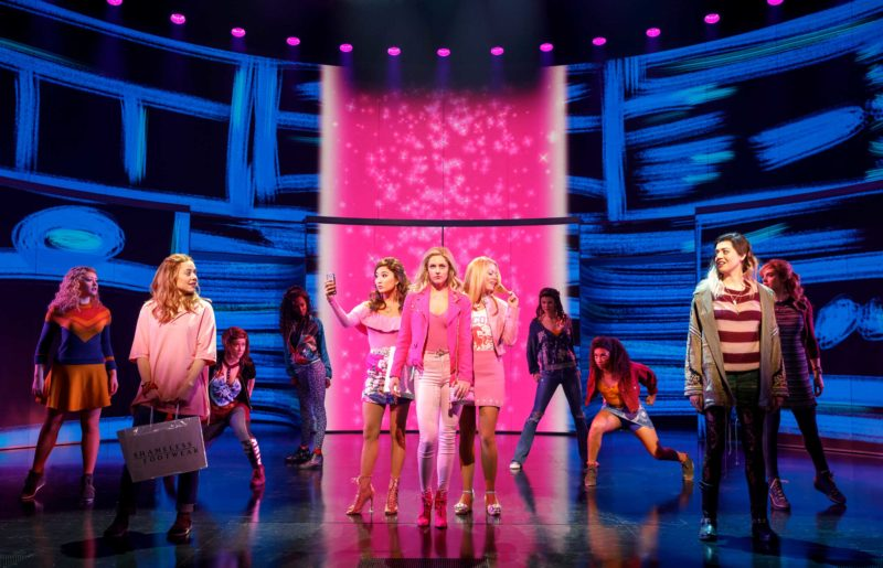 The Plastics - Gretchen (Ashley Park), Regina (Taylor Louderman), and Karen (Kate Rockwell) - strut through the halls of the high school as students, including Cady (Erika Henningsen) and Janis (Barrett Wilbert Weed), look on in a scene from Mean Girls.