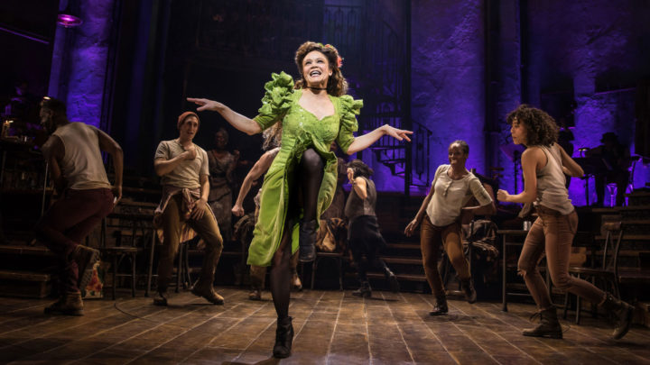 A brunette dances center stage in a green dress and black stockings surrounded by the company of Hadestown on Broadway dressed clothing worn by blue collar workers in shades of beige